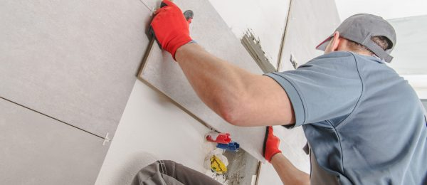 Caucasian Ceramic Tiles Installer in His 30s Creating Brand New Wall of Modern Wide Format Tiles Inside Residential Bathroom. Professional Remodeling Job.