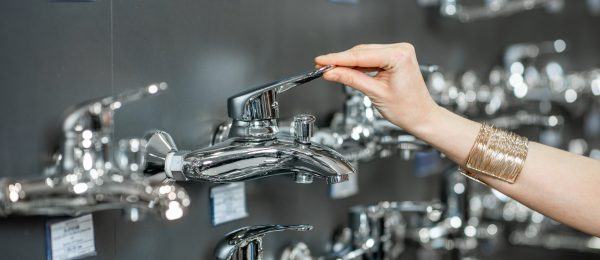 Woman choosing sanitary taps, close-up view on the hand touching tap on the showcase of plumbing shop